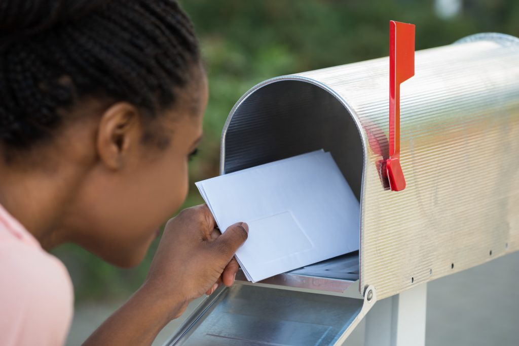 Woman Putting Letter In Mailbox - effective direct mail