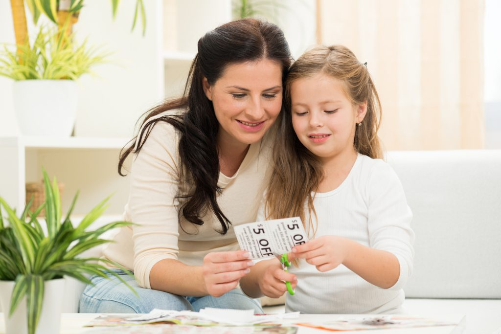 Family Making Shopping list and coupons for modern mail and direct mail