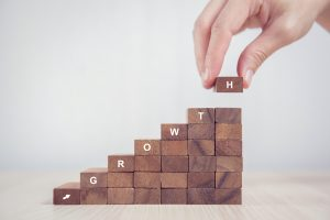 Close up Woman hand arranging wood block stacking as step stair. Business concept growth success process for ways to improve your campaign.