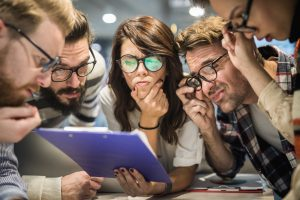 Group of thoughtful business millennials, analyzing a direct mail marketing and millennials campaign with eyeglasses reading documents in the office.