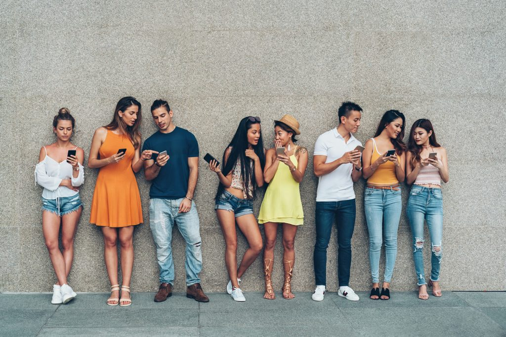 Group of young people with smart phones standing in a row outdoors against a wall