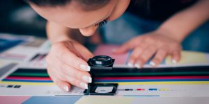 Worker in printing and press centar uses a magnifying glass - offset printing